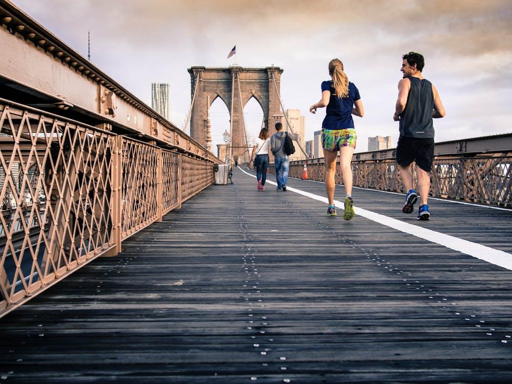 People running across a bridge