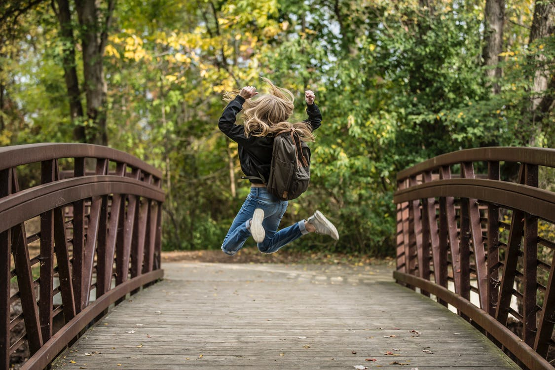 Person jumping for joy on a bridge