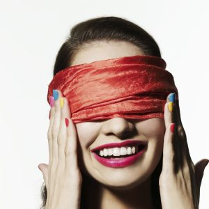 Woman wearing a pink blindfold