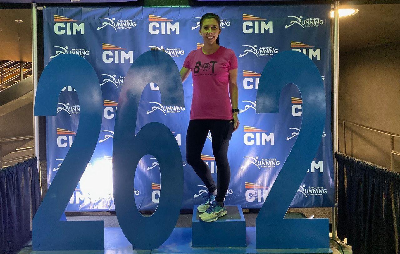 Jessica standing on a podium after finishing the CA International Marathon
